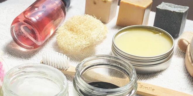 A variety of natural skin care products, soap bars, coconut oil, toner loofah, salves and more laid out on a whit towel.