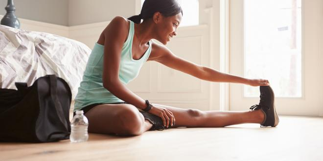 Young black woman sitting on the floor at home stretching.