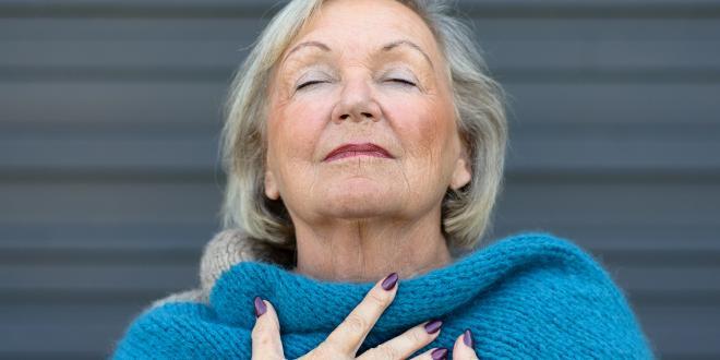 an older woman taking a deep, clear breath