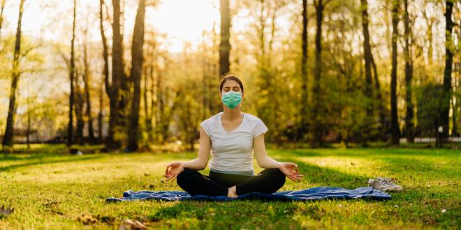 a woman wearing a mask, meditating in a sunny park