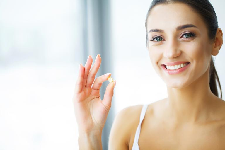 Woman with glowing healthy skin about to take her fish oil supplement